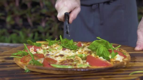 Close up cutting pizza on slices with roller knife on wooden table in pizzeria. Chef cook slicing hot pizza in italian restaurant. Preparation traditional italian food. National food concept.