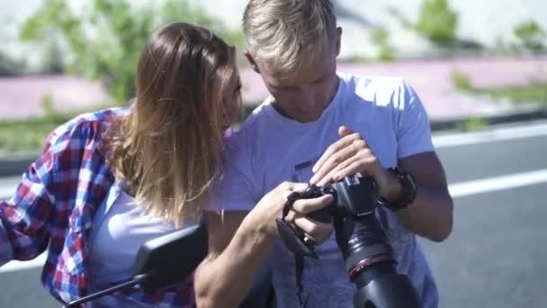 Žena foto model a fotografa Foto při pohledu na fotoaparát při focení. Fotograf a mladá modelka sledování obrazu. Muž a žena pomocí fotografické kamery pro sledování videa.