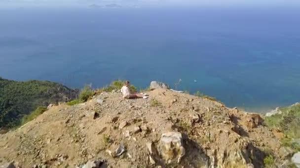 Turista na okraji útesu s výhledem na krajinu modré moře z létající dron. Letecký pohled na tyrkysové moře a hory. Krásný modrý oceán krajina od vrchol hory