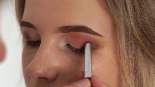 Dekorativní kosmetika oči oční stíny zblízka. Vizážistiku používající kosmetický štětec pro aplikaci eyeshadows na víčku mladá žena. Maskérka použití kosmetiky na obličej žena. Krása a móda