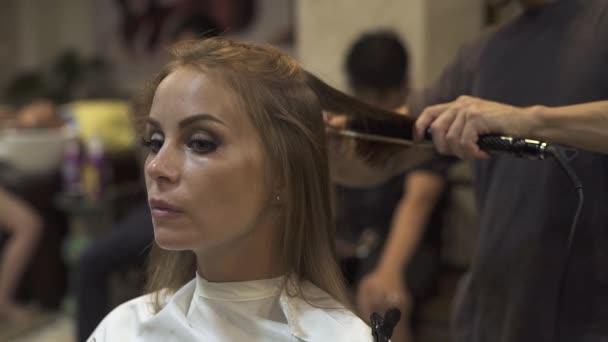 Mladá žena při narovnávání vlasů v salonu krásy. Kadeřník, používající žehlička na vlasy a hřebínek pro ženu kadeřnictví v Kadeřnické studio. Kadeřnice, vytvoření ženský účes pomocí kleští a hřeben