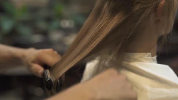 Kadeřník, česání vlasy a rovnání s žehlička na vlasy a kadeřnictví v salonu krásy. Žena účes v kadeřnictví studio. Kadeřník, vytváření účes pro dlouhé vlasy ženu v holičství