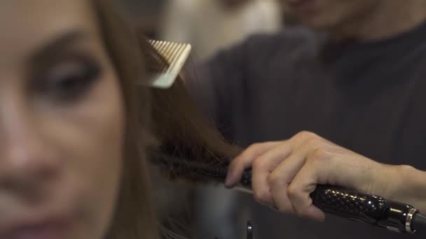Barber combing hair and straightening with hair iron while hairstyling in beauty salon. Woman hairstyle in barbershop. Hairstylist creating hairstyle for long haired woman in hairdressing studio.