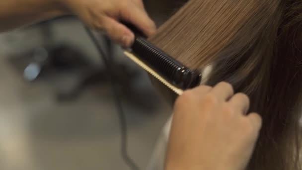 Dlouhé vlasy kadeřnictví s vlasy železa v profesionální kosmetické studio. Kadeřník dělá rovnání pro dlouhé vlasy žena v holičství. Kadeřník vytváření účesu bruneta žena