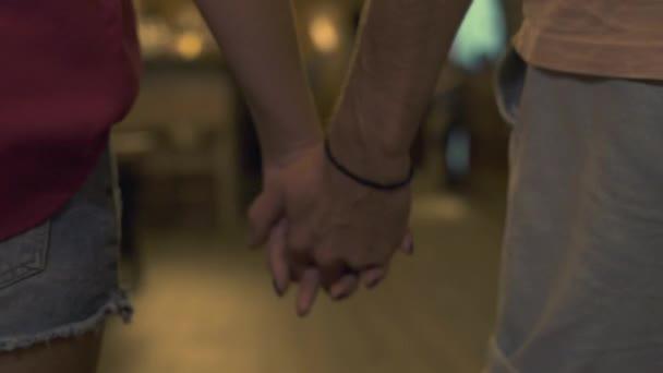 Fiatal férfi és a nő kezét, és a gyaloglás a étterem közelről. A pár a szerelem barátnője és a barátja tartja kezében a kávézó este. Romantikus kapcsolatok és az emberek kötés.