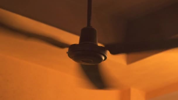 Ceiling fan rotating in room and air circulation close up. Slow motion electric ceiling fan for air ventilation and cooling in home interior.