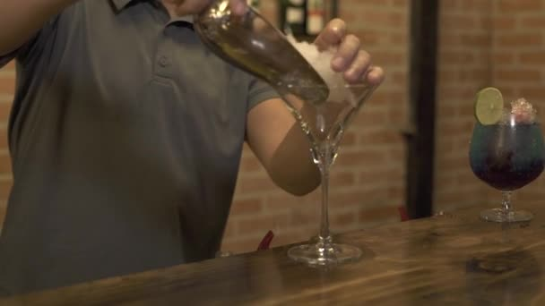 Barman putting crushed ice in glass for making cocktail at bar counter of restaurant. Bartender preparing alcoholic cocktail with ice in glass at bar table while evening party.