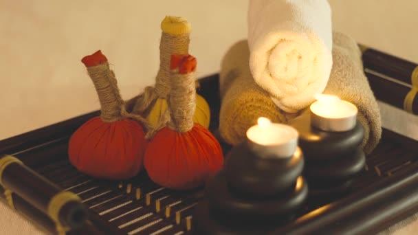Složení lázně, svíčky, kameny pro masáž těla, aromatické byliny a ručníky. Zblízka. Masážní dekorace se svíčkou a kameny ve spa salonu. Zen a koncepce