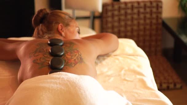 Junge Frau Genuss hot Stone Massagen im Beauty-Spa-Salon. Stone-Behandlung und Körper massage-Therapie. Zen und Konzept zu entspannen. Körper und Haut Pflege im Wellness-salon
