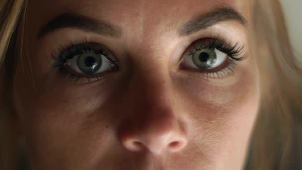 Közelről nő arcát, nyitott szemmel kacsintás, és keresi, hogy kamerát. Portré szomorú nő. Női arc, a szemek, a szempillák és a eyesbrows. Természetes szépség és a smink.