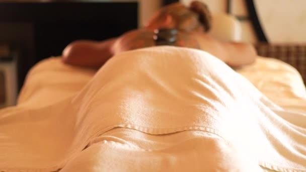 Krásná žena relaxační wellness salonu na horké kamenné masáž. Stone léčby a masážní terapie. Zen a relaxovat koncept. Tělo a péče o pleť ve spa salonu.