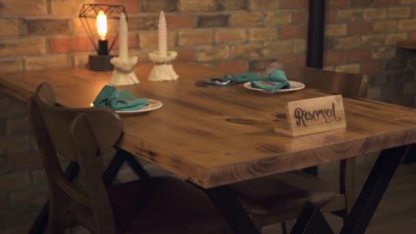 Servírka slouží jídelní stůl s nápisem rezervováno pro romantické rande. Servírka Příprava vyhrazen stůl pro večeři s svíčka v módní kavárně. Koncepce interiéru restaurace.