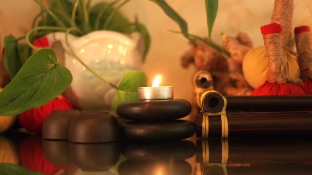 Wellness-Komposition brennende Kerzen, Steine für Körpermassage, aromatische Kräuter und Tasse für Teezeremonie. hautnahe Massagedekoration mit Kerzen und Steinen im Beauty-Spa. Zen und Relax-Konzept.