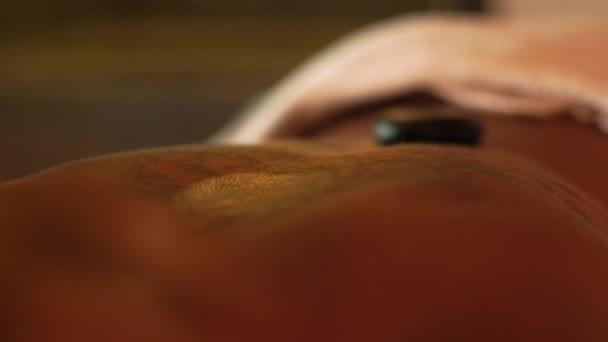 Stone masáž v lázních Krása Detailní záběr. Mladá žena, relaxaci a masáž s lávovými kameny. Lázeňská léčba v resortu. Péče o tělo a pleť. Alternativní zdravotnictví a medicína.