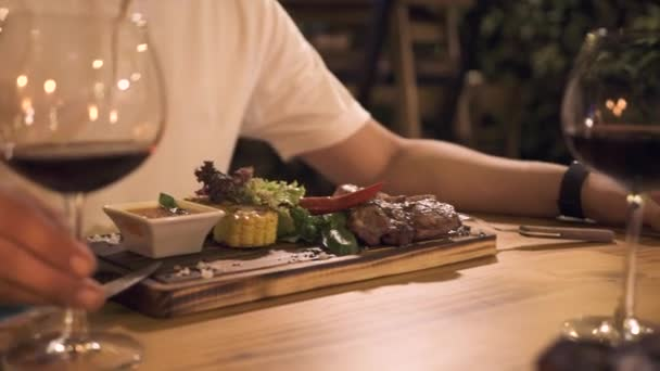 Male hand holding wine glass at evening dinner in grill restaurant. Peole dinning grilled meat steak in barbeque restaurant.