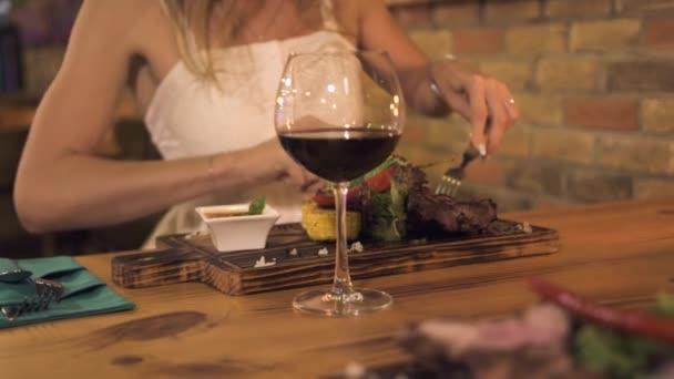 junge Frau schneidet gegrilltes Fleisch mit Messer und Gabel während des Abendessens im Grillrestaurant. Frau isst Fleischgrill in Café aus nächster Nähe.
