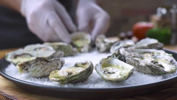Ústřice zapečený se sýrem a bylinkami na desku v rybí restauraci. Jídlo na pozadí. Šéfkuchař vaří zdobení ústřice. Restaurace menu a moře potraviny složení. Zdravá výživa koncept.
