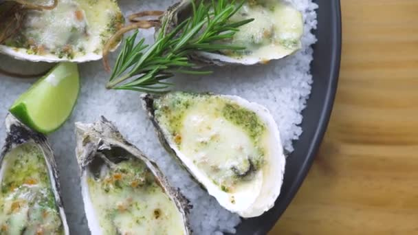Oysters baked with cheese, lime and herbs on plate. Presentation menu seafood restaurant. Mediterranean cuisine. Serving seafood composition top view. Healthy nutrition concept.