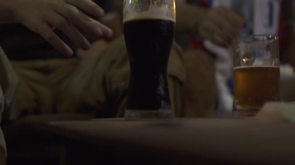 Young man drinking dark beer from glass in bar pub close up. Portrait man drinking cold beer from glass in sport bar.