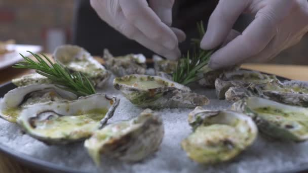 Food design styling concept. Chef cook decorating oysters with rosemary on plate. Food decotation in seafood restaurant. Seafood dishes in luxury restaurant.