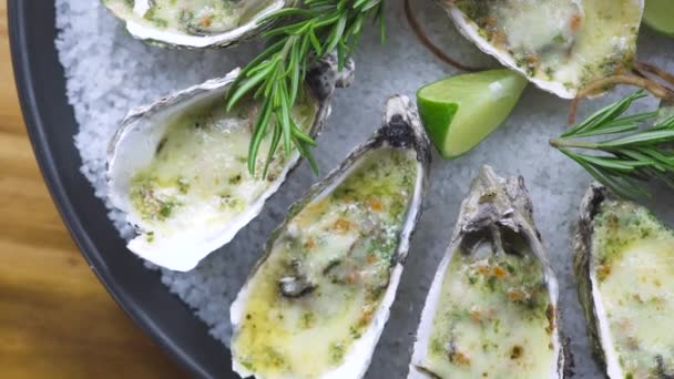 Oysters baked with cheese, lime and herbs on plate. Menu seafood restaurant. Mediterranean cuisine seafood composition top view. Healthy nutrition concept.