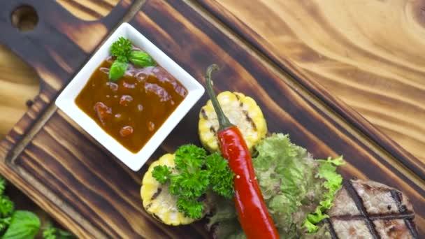 Grilované maso steak složení. Grilovaný steak s feferonka, byliny, obilí a rajskou omáčku na dřevěné desce. Jídlo pozadí na dřevěné kopie prostoru. Zdravá výživa a dietní koncepce.
