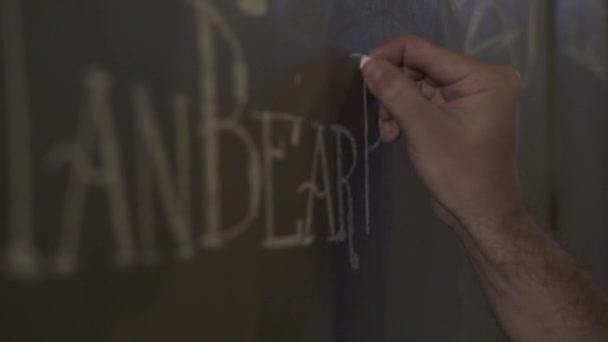 Male hand drawing chalk on black board beer menu in bar pub. Waiter writing menu on chalk board in restaurant. Drawing price in brewery bar.