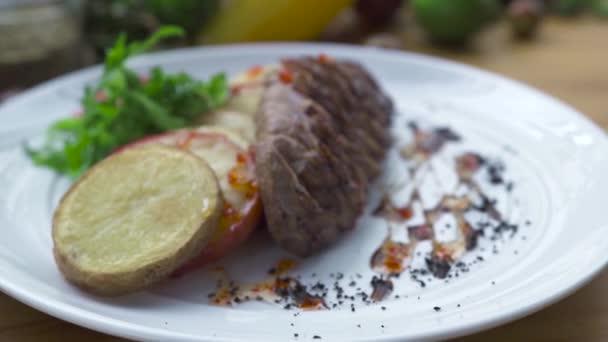 Grilované maso steak se smaženými brambory na bílé plotně zblízka. Složení potravin plátky bbq masa se zeleninovou oblohou na desce. Jídlo design ve vysoké kuchyně. Nabídka restaurace Gril.