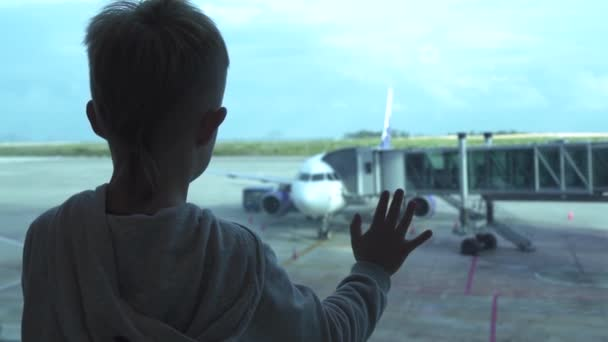 Little boy looking to airplane from airport window while waiting in departure lounge. Boy tourist looking to aircraft from airport terminal window on waiting area. Travel and tourism concept.