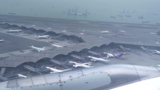 Pohled z okna, letící letadla nad letištěm a moře. Křídla letounu letícího nad lodí v modrém oceánu. Pohled z okna letadla. Cestování letadlem, letadla.