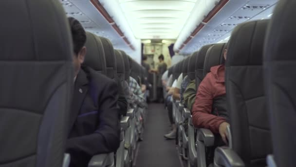 Cestující sedí na sedadlech letadla při letu v obloze. Cestující uvnitř kabiny komerční letadlo během letu. Cestování letadlem moderní komerční letadlem.