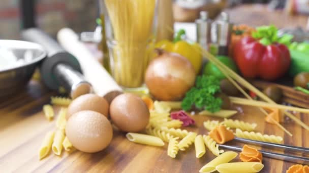Spaghetti and macaroni with ingredients for cooking pasta on wooden table. Fresh vegetable and eggs for cooking italian pasta and sauce on wooden table. Italian food composition.