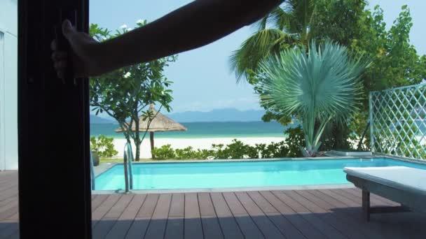 Aussichtspunkt Ausgang zur Veranda mit Schwimmbad auf Meeresstrandlandschaft. Blick aus dem Fenster auf den Pool auf Luxus-Villa am Meeresstrand, blaues Wasser und Palmen Hintergrund.