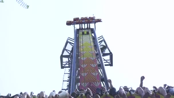 People riding on extreme attraction in amusement park. Happy friends having fun on thrilling roller coaster ride in amusement park.