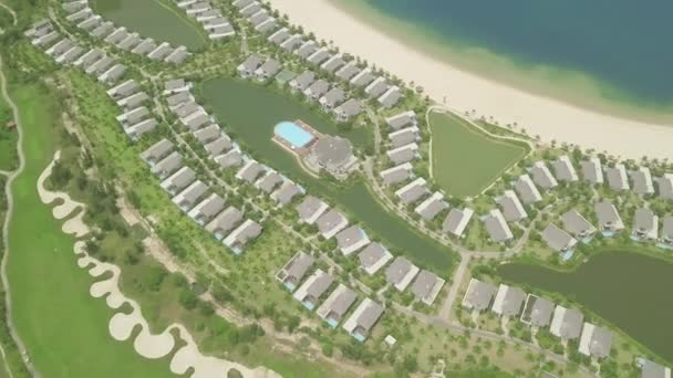 Modern cottage village with luxury mansion on lake shore, green lawn background. Aerial view architecture luxury village with houses, swimming pool and golf course.