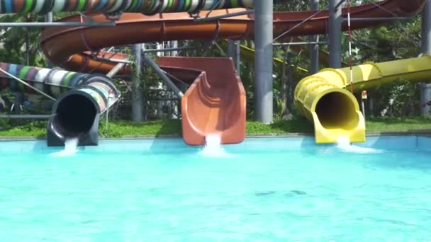Colorful water tube and water slides in blue swimming pool in summer aquapark. Outdoor waterpark in amusement park.