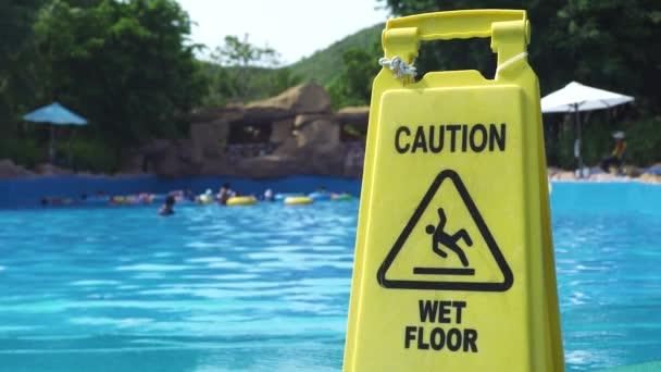 Žlutá varovná cedule na pozadí bazénu v zábavním aquaparku. Varování mokré podlahy znamení v aqua parku na pozadí bazénu.