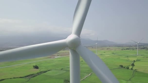 Wind power turbines drone view. Wind generator for clean renewable energy aerial view. Windmill turbine in green field on cloudy sky and mountain landscape. Alternative sources renewable energy.