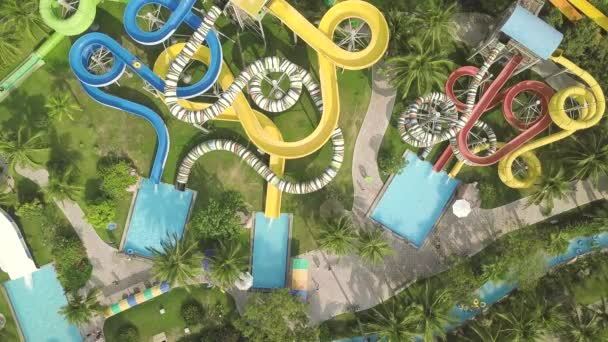 Colorful water slide in amusement aquapark. Aerial view. People having fun riding on slides in outdoor water park at summer vacation