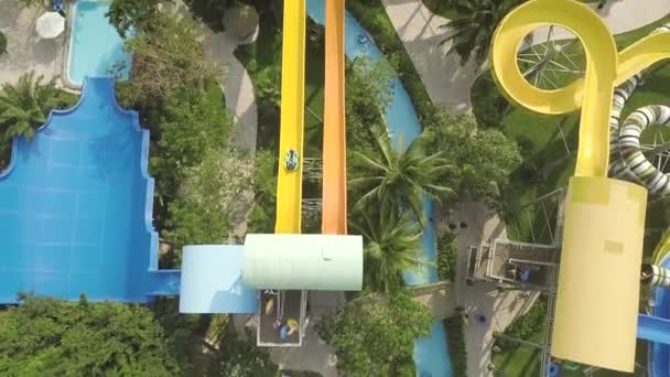Colorful water slides in amusement aquapark at summer vacation. Aerial view. People having fun riding on slides in outdoor water park at summer vacation.