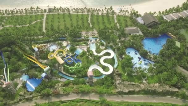 Colorful water slides in amusement aquapark on sea beach landscape. Aerial view. People having fun riding on slides in outdoor water park at summer vacation.