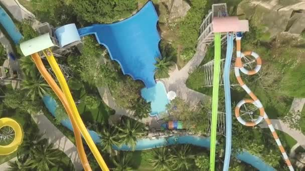 Colorful water slides in amusement aquapark. Aerial view. People having fun riding on slides in outdoor water park at summer vacation.