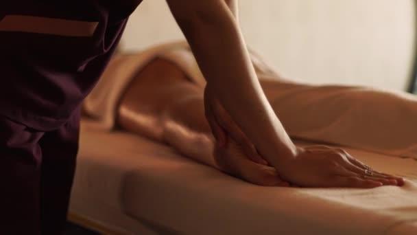 Masseur csinál lábak masszázs olajjal a fiatal nő Resort Spa szalon. Fiatal nő kap testmasszázs luxus spa központ. Testápolás és bőrápolás.