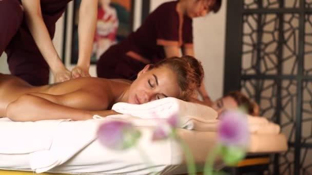 Krásná žena, která dostává masáž s olejem v lázeňském salónu. Mladá žena, která dostává tělesnou masáž v luxusním lázeňském centru. Tělesná relaxace a péče o pokožku.