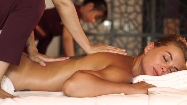 Gyönyörű nő kapok hátmasszázs olajjal üdülőhely Spa szalon. Fiatal nő kap testmasszázs luxus spa központ. Testápolás és bőrápolás.