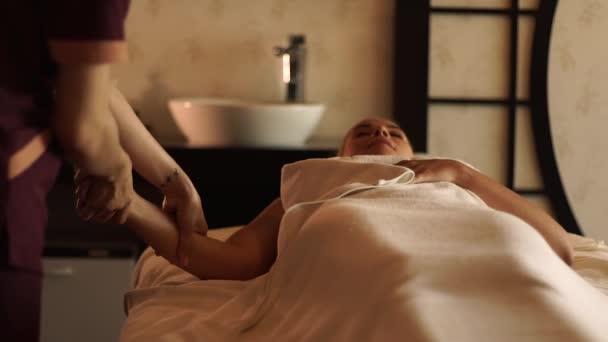 Mladá žena dostává masáž těla olejem v lázeňském salonu. Mladá žena dostává masáž rukou v luxusním lázeňském centru. Tělesná relaxace a péče o pleť.