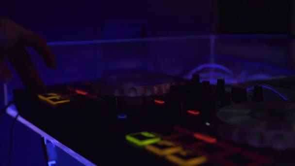Professional dj equipment for mixing and record house music on dance party in night club. Close up audio equipment and DJ control music console with colorful light in nightclub.
