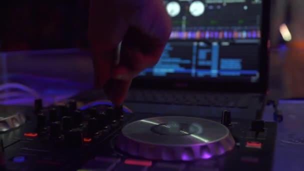 DJ zenei konzol keverő tánczene és laptop a disco klubban. DJ keverő játékos és hang konzol dance party. Közeli lemezlovas vezérlő zenei hangszínszabályzóval a keverő fedélzeten az éjszakai klubban.