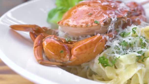 Italian seafood pasta with red crab, fresh herb seasoning and cheese on white plate on wooden table. Serving size traditional pasta with seafood in restaurant. Traditional italian cuisine.