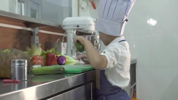 Chlapeček kuchař vaří v zástěře a kuchařku v kuchyni v restauraci. Zvláštní kuchařka na dřevěné desce v komerční kuchyni. Děti na vaření potravin.